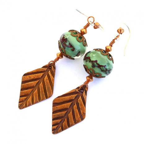 Handmade earrings created with copper leaves and green lampwork glass beads.