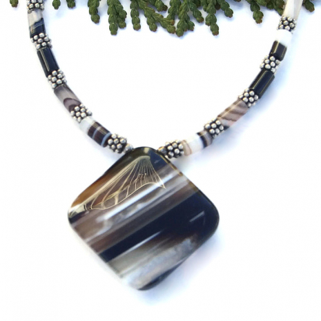 The banded agate pendant features diagonal stripes of black, white and taupe.