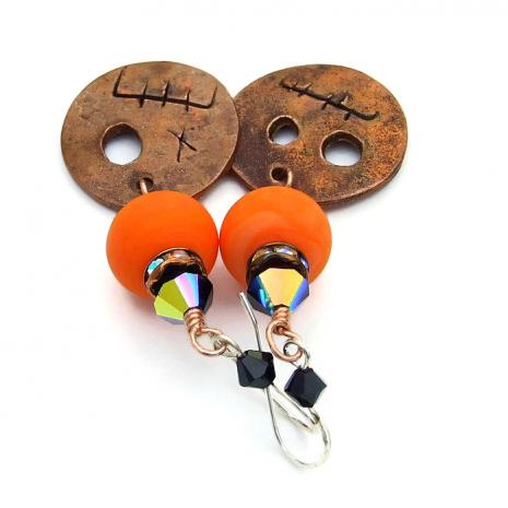 Goblin face earrings with orange lampwork.