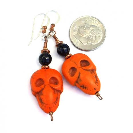 Halloween orange and black skull earrings for her.
