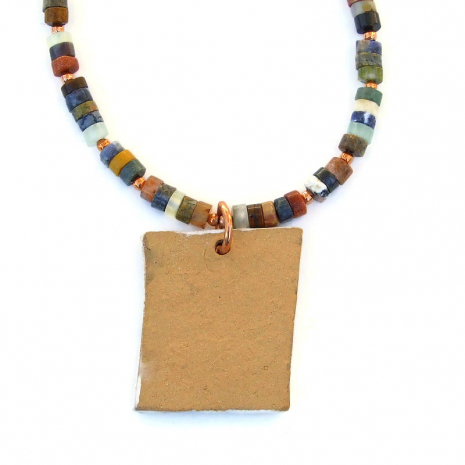 unglazed back side of ceramic horse dream pendant